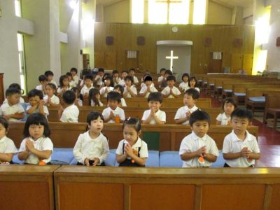 聖歌「水のこころ」を歌い、お祈りをする園児たち