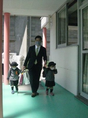 昇降口に向かってテラスを歩く姉弟
