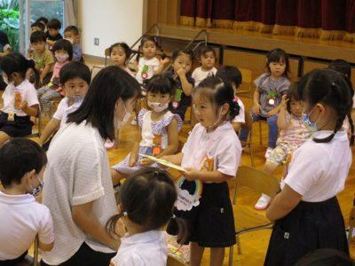 担任の先生からプレゼントをもらうひよこ組。うらやましそうにいちご組のいちご組のお友達も見ています。