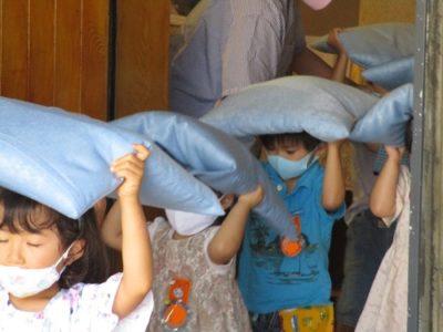 地震の合図で、座布団を頭に園庭に避難する園児たち