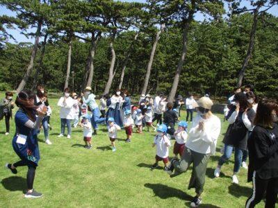 海辺の芝生広場に集まって、みんなで体操