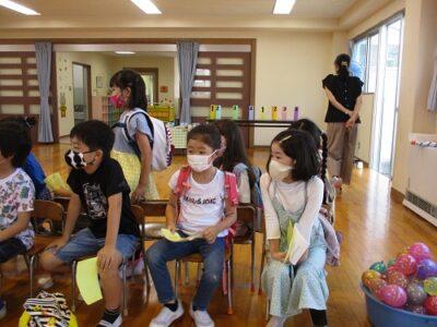 ホールに集まって、6つのゲームのやり方の説明を聞く子ども達