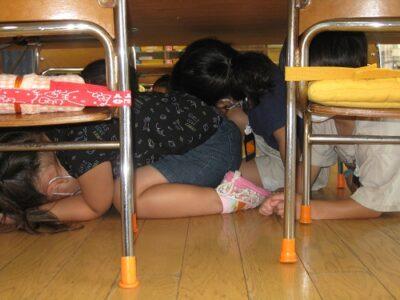 地震の合図で、みな机の下に隠れました。